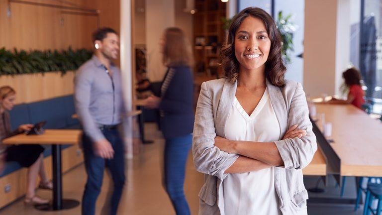 Portrait Of Businesswoman Standing In Busy Modern Open Plan Offi